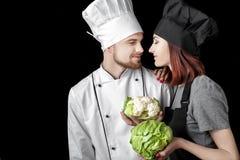 黑人制服和人厨师的妇女厨师白色一致的举行新鲜的嫩卷心菜和花椰菜的在黑背景 免版税库存照片