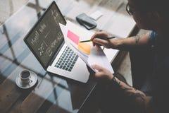 年轻人刺字了工友与膝上型计算机一起使用在办公室 商人分析在手上的文件 图表,网上接口 图库摄影