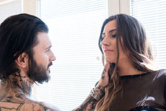 年轻人刺字了接触一名性感的妇女的面孔人 库存图片