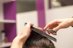 年轻人剪在理发店的头发 免版税库存图片
