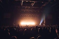 人剪影一明亮的在阶段前面的流行音乐摇滚乐音乐会 有姿态垫铁的手 那晃动 在a的党 免版税库存照片