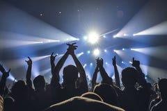 人剪影一明亮的在阶段前面的流行音乐摇滚乐音乐会 有姿态垫铁的手 那晃动 在a的党 免版税库存图片