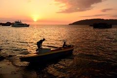 人剪影一条小船的在亚庇 免版税库存图片