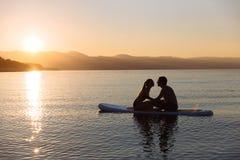 人剪影和亲吻在一口的年轻性感的女孩在海洋在阳光下冲浪 概念生活方式,体育,爱 图库摄影