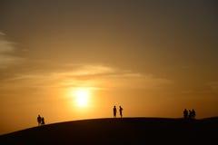 人剪影在反对落日的沙漠 免版税库存图片