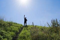 人剪影在明亮的阳光下在顶部台阶 免版税图库摄影