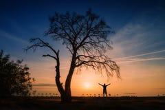 人剪影在海滩的树下 免版税库存照片