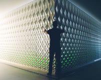 人剪影在轻和黑暗的墙壁前面的 免版税库存图片
