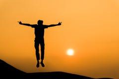 人剪影愉快的跃迁的在橙色日落天空 免版税图库摄影