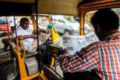 人力车计程车车站在本地治里市,印度 读报纸的司机 免版税库存照片