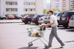 人劳斯在停车处的购物车 库存照片