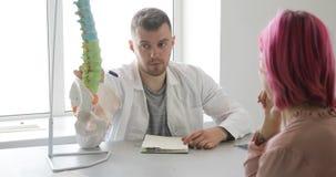 人医生解释治疗计划给使用脊椎模型的患者 股票录像
