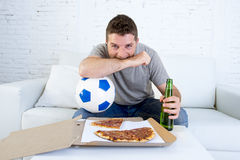 年轻人单独举行的球和啤酒瓶观看的橄榄球赛在电视在家沙发长沙发 库存照片