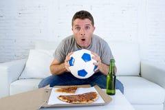 年轻人单独举行的球和啤酒瓶观看的橄榄球赛在电视在家沙发长沙发 图库摄影