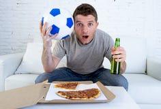 年轻人单独举行的球和啤酒瓶观看的橄榄球赛在电视在家沙发长沙发 免版税图库摄影