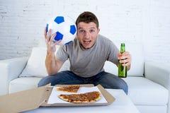 年轻人单独举行的球和啤酒瓶观看的橄榄球赛在电视在家沙发长沙发 库存图片