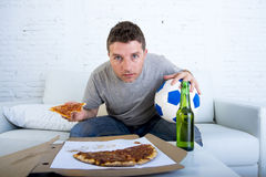 年轻人单独举行的球和啤酒瓶观看的橄榄球赛在电视在家沙发长沙发 免版税库存图片
