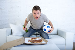年轻人单独举行的球和啤酒瓶观看的橄榄球赛在电视在家沙发长沙发 免版税库存照片