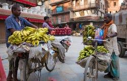 人卖在一辆自行车的香蕉在街市上 免版税库存图片