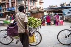 人卖在一辆自行车的香蕉在街市上 库存图片