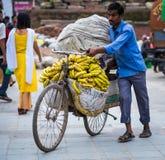 人卖在一辆自行车的香蕉在街市上 图库摄影
