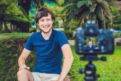 年轻人博客作者在公园记录在照相机前面的录影 免版税库存照片