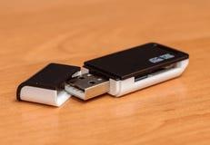 黑人卡片阅读机支持与USB的SD在木桌上 免版税库存图片