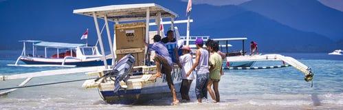 人卸载从速度木小船的物品到Gili空气,天堂海岛在印度尼西亚 库存照片