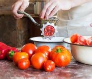 人厨师研成熟蕃茄片断入烹调的自创调味汁,番茄酱一台老葡萄酒手研磨机 免版税库存照片