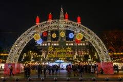 人参观在城镇厅附近的圣诞节市场晚上 免版税库存图片