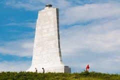 人参观在莱特兄弟全国纪念品的花岗岩塔 免版税库存图片