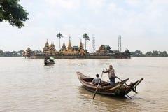 人发怒仰光河乘小船为在Ye Le Paya塔祈祷在小海岛上的浮动塔 免版税图库摄影