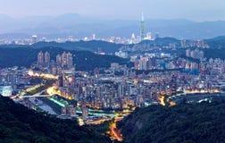 人口过剩的郊区社区空中全景在黄昏的台北有台北101在X的塔在街市&桥梁看法  免版税库存照片