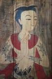 人古老传统绘画有服装的在木棕色背景,泰国在木头的样式常设男性图画 免版税库存照片