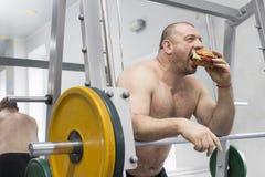 人吃一个汉堡包用肉和乳酪在健身房 免版税图库摄影