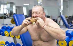 人吃一个汉堡包用肉和乳酪在健身房 图库摄影