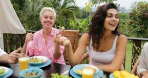 人吃健康素食食物,朋友通信的小组谈话在表上坐热带大阳台 股票视频
