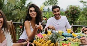 人吃健康素食食物,朋友通信的小组谈话在表上坐热带大阳台Pov 股票录像