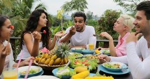 人吃健康素食食物,朋友通信的小组谈话在表上坐热带大阳台Pov 股票视频