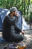 人吃在灼烧的煤炭、菜、夏南瓜和蘑菇的可口烤素食串在酱油 野营的食物 图库摄影