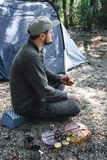 人吃在灼烧的煤炭、菜、夏南瓜和蘑菇的可口烤素食串在酱油 野营的食物 库存图片