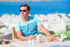 年轻人吃早餐在室外咖啡馆有在米科诺斯岛镇的惊人的看法 在豪华旅馆大阳台的人饮用的咖啡 库存照片