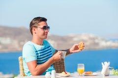 年轻人吃早餐在室外咖啡馆有在米科诺斯岛镇的惊人的看法 在豪华旅馆大阳台的人饮用的咖啡 免版税图库摄影