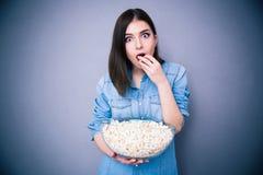 年轻人吃玉米花的惊奇的妇女 库存照片