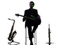 人吉他弹奏者演奏剪影的低音歌手球员 免版税图库摄影