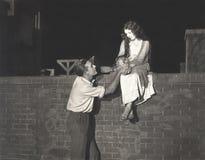 人向求爱的妇女坐砖墙 免版税图库摄影