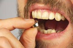 人吞下电池,举行在手指的batery, si 免版税库存照片