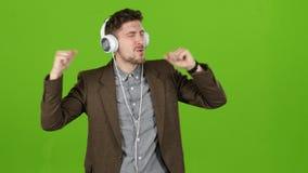 人听到在耳机和舞蹈的精力充沛的音乐 绿色屏幕 股票录像