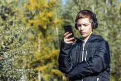 人听到在耳机的音乐并且调查他的电话在一晴朗的秋天天以树为背景 免版税图库摄影