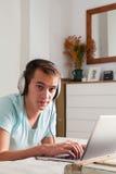 年轻人听的音乐在家 他在与膝上型计算机的床上在 库存照片